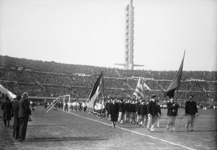 "Inaugural ceremony of the Centenario Stadium. Delegations parade. At the rear end, the ""Olímpica"" stand and the ""Homage Tower."" July 18th, 1930."