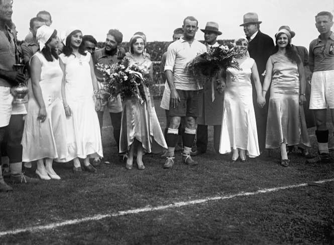 "Just before the beginning of the semi-final between Uruguay and Yugoslavia, five pupils of the ""Instituto Nacional de Señoritas"" (Young Ladies' Finishing School) wearing dresses bearing the colours of the national flag- a golden one, two white ones and two blue ones- give bouquets to the captains of the respective teams, José Nasazzi and Milutin Yokovitch. Centenario Stadium. July 27th, 1930."